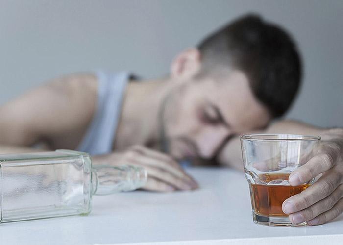 алкоголик в запое лежит на столе со стаканом